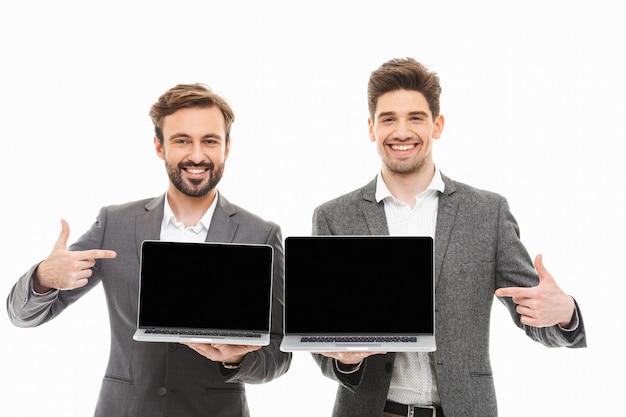Retrato de dois homens de negócios felizes apontando os dedos