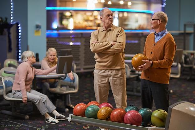 Retrato de dois homens sêniors jogando boliche com amigos em segundo plano, enquanto desfrutam de entretenimento ativo na pista de boliche, copie o espaço