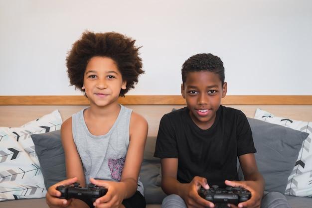 Retrato de dois irmãos afro-americanos jogando videogame em casa. conceito de estilo de vida e tecnologia.