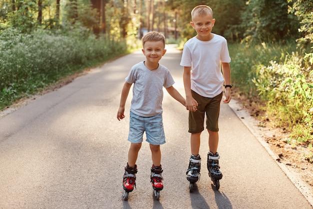 Retrato de dois irmãos de meninos sorridentes, vestindo camisetas de estilos casuais e shorts, andando de patins na bela natureza na estrada, crianças de patins, olhando para a câmera, passando o tempo livre de forma ativa.