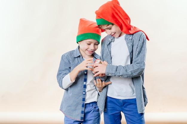 Retrato de dois irmãos felizes em bonés vermelhos de papai noel