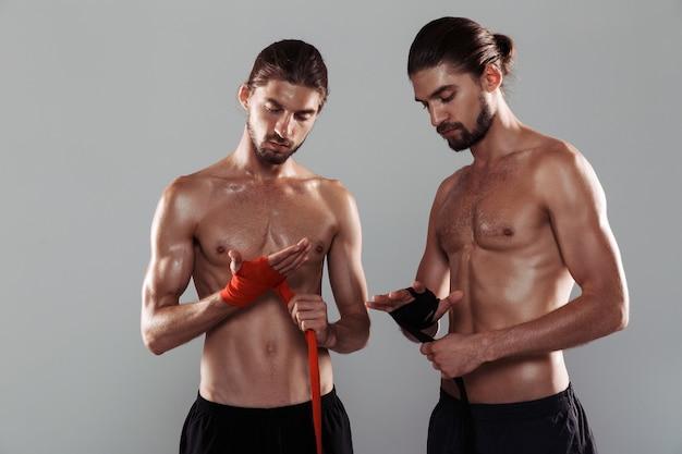 Retrato de dois irmãos gêmeos musculosos sem camisa