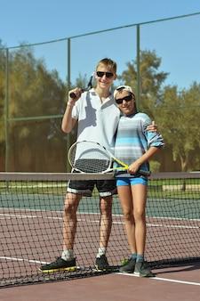Retrato de dois irmãos jogando na quadra de tênis