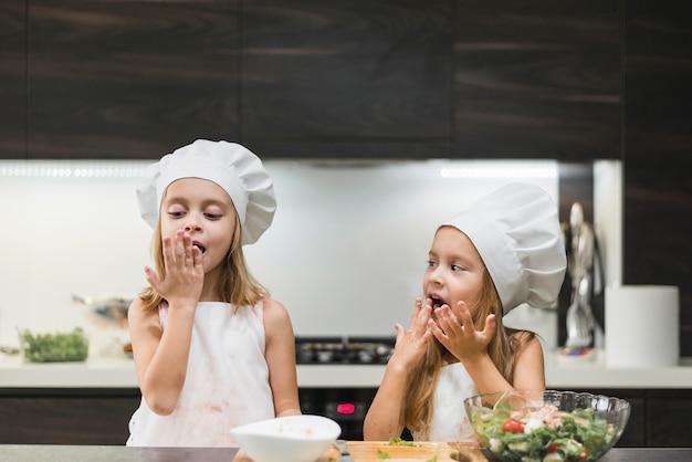 Retrato, de, dois, irmãs, lamber, seu, mãos, enquanto, preparar, alimento