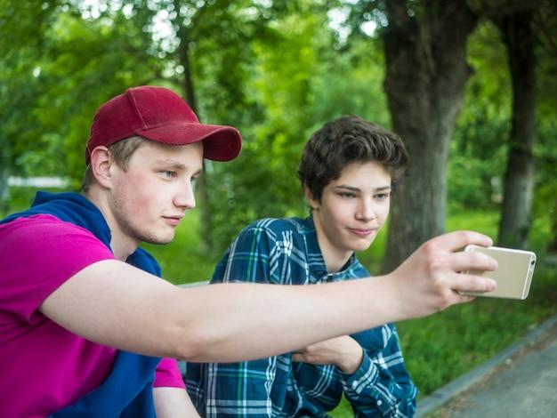 Retrato, de, dois, jovem, sorrindo, bonito, irmãos, ao ar livre, fazendo, um, selfie, com, telefone, parque