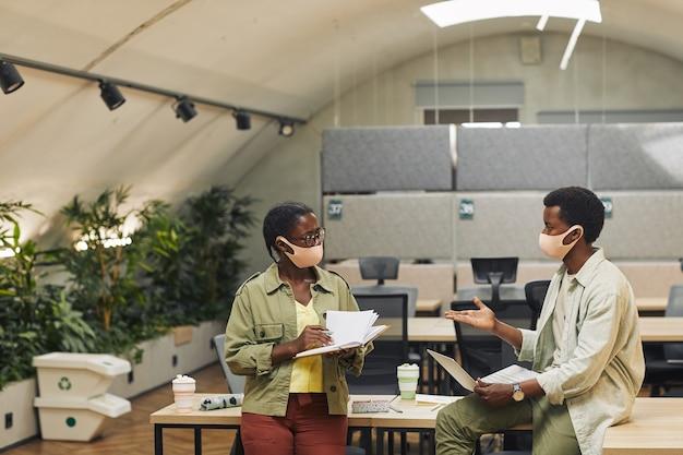 Retrato de dois jovens afro-americanos usando máscaras enquanto trabalhava em um escritório pós-pandêmico e discutia o projeto, copie o espaço