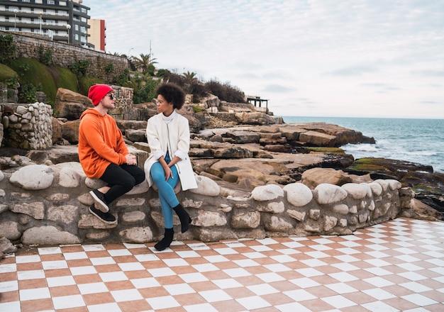 Retrato de dois jovens amigos a passar bons momentos juntos e a ter uma conversa enquanto está sentado com o mar no espaço.