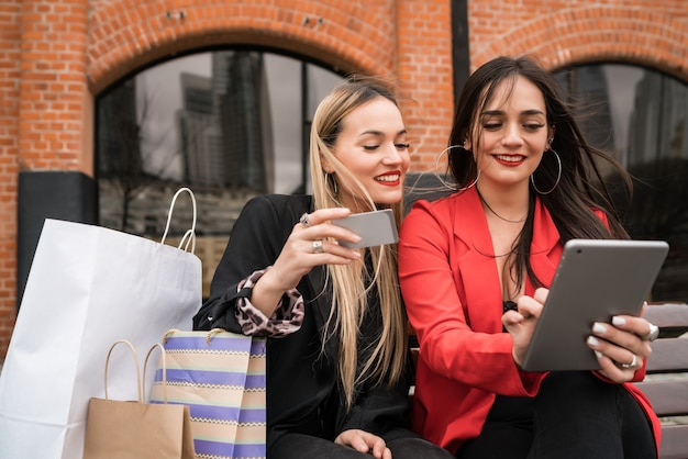 Retrato de dois jovens amigos compras online com cartão de crédito e tablet digital enquanto está sentado ao ar livre. conceito de amizade e estilo de vida.