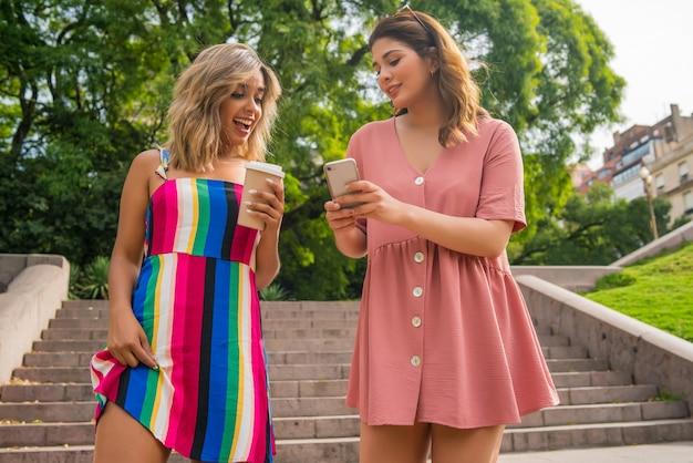 Retrato de dois jovens amigos olhando para o celular enquanto caminham ao ar livre