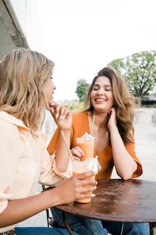 Retrato de dois jovens amigos passando um tempo juntos em um café ao ar livre. conceito urbano.