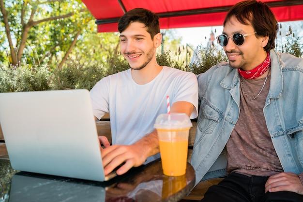 Retrato de dois jovens amigos usando um laptop enquanto está sentado ao ar livre em uma cafeteria