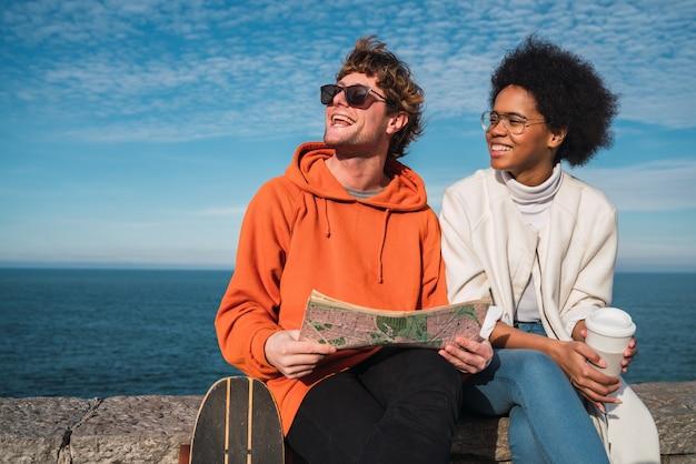 Retrato de dois jovens amigos viajando juntos, com um mapa e procurando direções. conceito de viagens.
