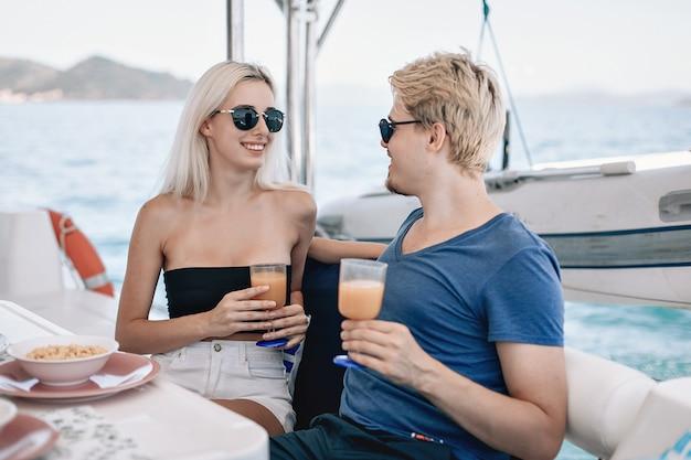 Retrato de dois jovens apaixonados namorado e namorada, bebendo em um café local em um iate.