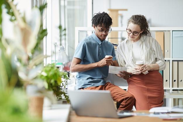 Retrato de dois jovens criativos olhando fotografias impressas durante a pausa para o café em um escritório moderno, copie o espaço
