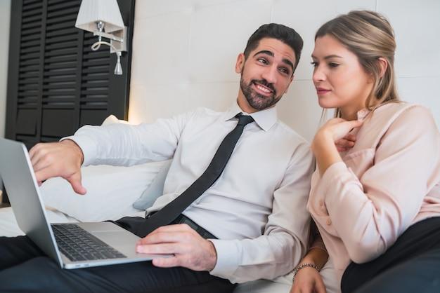 Retrato de dois jovens empresários trabalhando juntos no laptop no quarto do hotel. conceito de viagens de negócios.