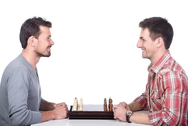 Retrato de dois jovens estão jogando xadrez.