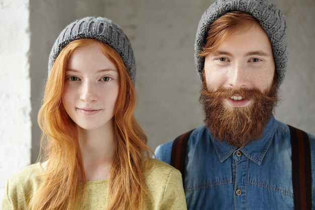 Retrato de dois jovens lindos caucasianos usando chapéus de malha cinza enquanto descansava dentro de casa.