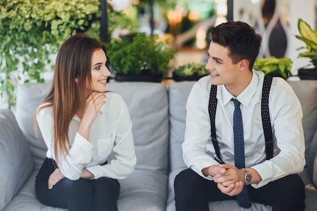 Retrato de dois jovens trabalhadores se comunicando no escritório, na esplanada