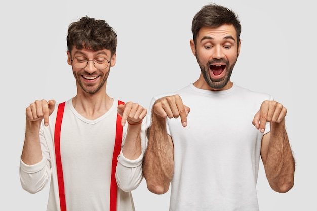 Retrato de dois lindos amigos do sexo masculino alegres com barbas e expressões alegres, indicadas no chão