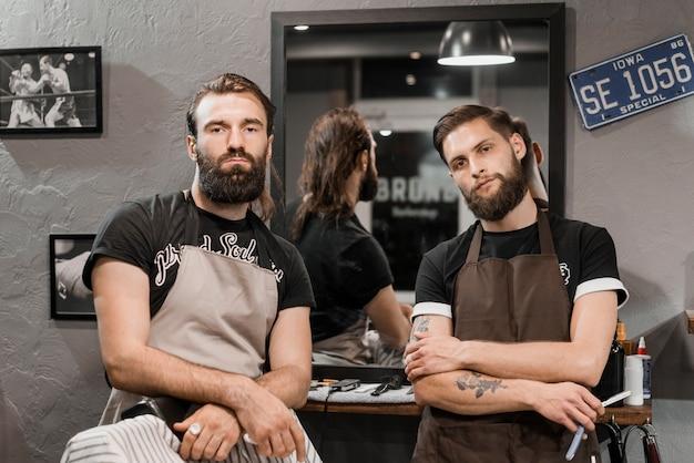 Retrato, de, dois, macho, barbeiros, olhando câmera