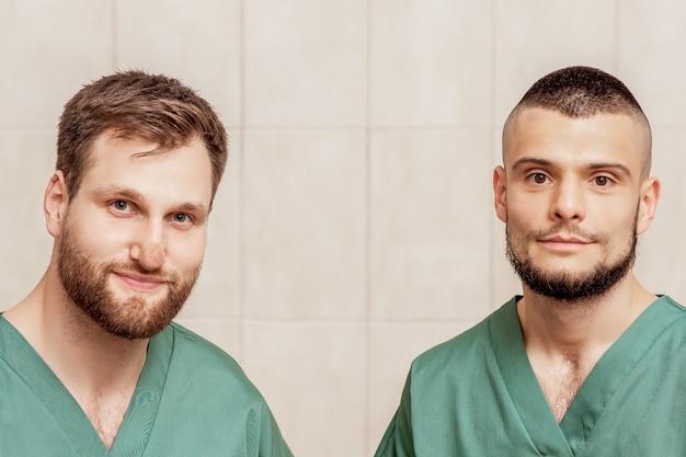 Retrato de dois massagistas masculinos ou médicos vestindo roupas de trabalho no local de trabalho.
