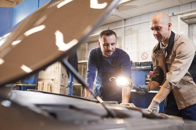 Retrato de dois mecânicos olhando sob o capô de um carro em uma oficina mecânica, copie o espaço da cintura para cima