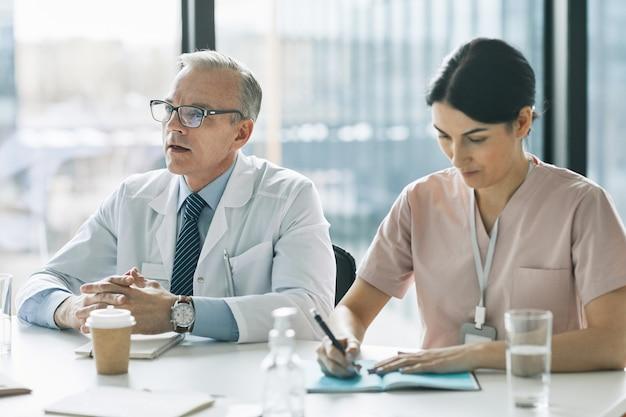 Retrato de dois médicos sentados em uma mesa de reunião perto da janela e fazendo anotações durante uma conferência médica