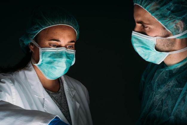 Retrato de dois médicos trabalhando usando máscara cirúrgica médica, tampa médica e roupas de proteção contra vírus