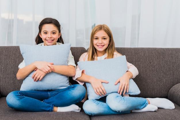 Retrato, de, dois, meninas sorridentes, sentar sofá, com, azul, almofadas, em, mão, olhando câmera