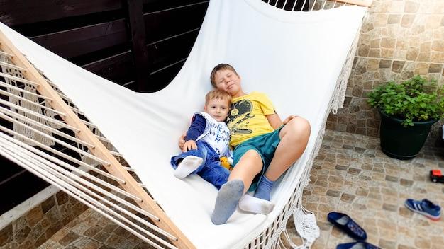 Retrato de dois meninos deitados na rede no quintal da casa