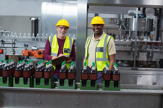 Retrato de dois operários monitorando garrafas de bebida gelada na fábrica