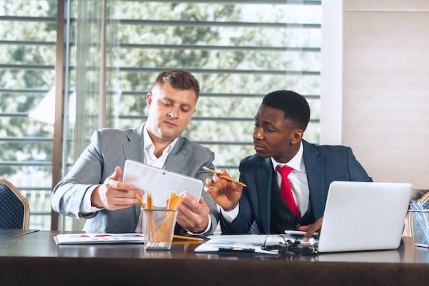 Retrato de dois parceiros de negócios, sentado em uma mesa juntos e trabalhando.