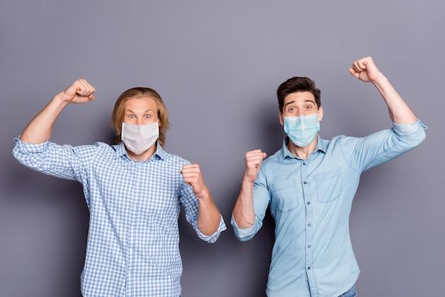 Retrato de dois rapazes alegres e alegres de sorte vestindo uma máscara respiratória de camisa xadrez, o melhor amigo, celebrando a vitória da infecção cobiçada, fundo cinza pastel