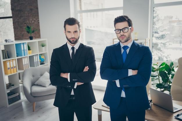 Retrato de dois simpáticos e atraentes homens experientes, elegantes e experientes, especialista em tubarão, empregador, escritório de advocacia, banqueiro, gerente de vendas, braços cruzados em branco claro interior estação de trabalho