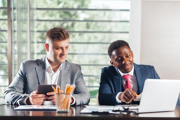 Retrato de dois sócios comerciais que sentam-se em uma tabela junto e que trabalham.