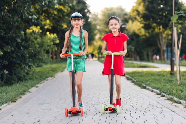 Retrato, de, dois, sorrindo, femininas, amigos, ficar, ligado, empurre scooter