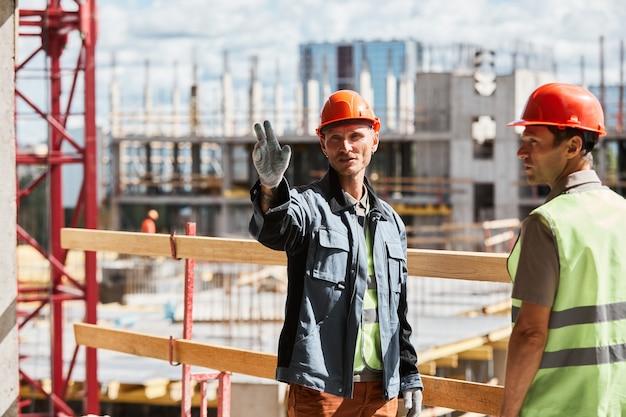 Retrato de dois trabalhadores da construção civil discutindo projeto em um prédio alto, copie o espaço