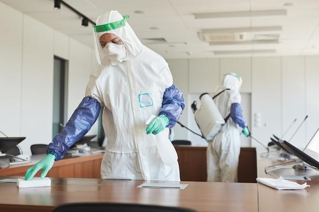 Retrato de dois trabalhadores de saneamento vestindo macacões anti-risco, limpando e desinfetando a sala de conferências no escritório