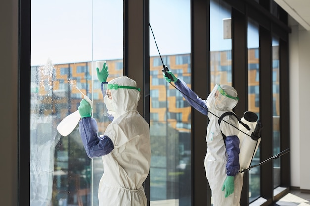 Retrato de dois trabalhadores vestindo roupas anti-perigosas, desinfetando as janelas do escritório à luz do sol,