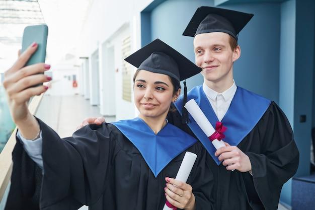 Retrato de dois universitários tirando uma selfie durante a cerimônia dentro de casa, copie o espaço da cintura para cima