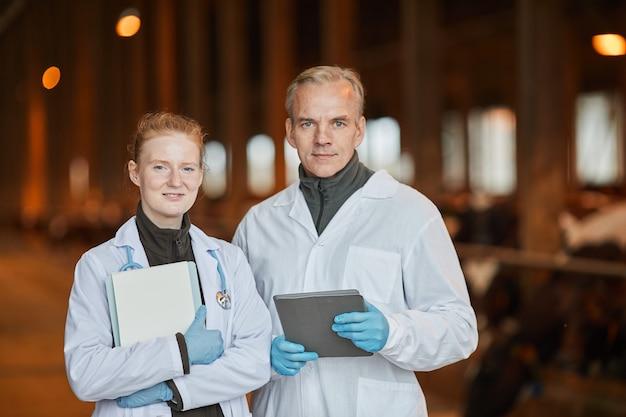 Retrato de dois veterinários sorridentes na fazenda, olhando para a câmera enquanto segura comprimidos, copie o espaço da cintura para cima