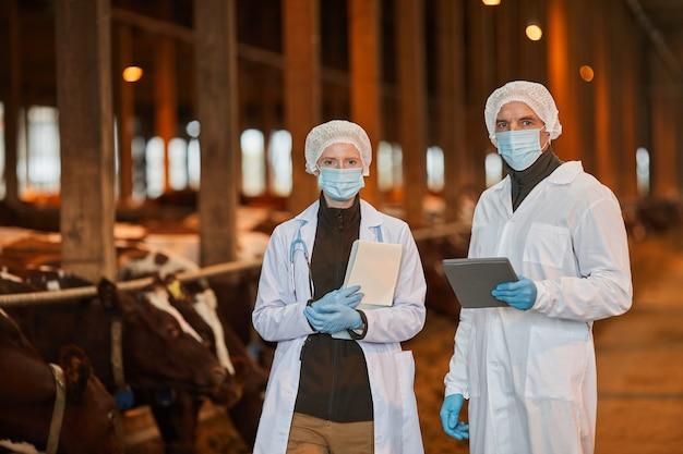 Retrato de dois veterinários usando máscaras na fazenda e olhando para a câmera segurando comprimidos, copie o espaço da cintura para cima