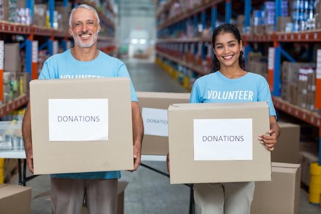 Retrato de dois voluntários segurando uma caixa de doações