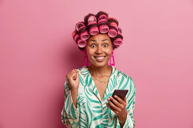Retrato de dona de casa feliz fecha o punho e sorri amplamente, vestida com robe doméstico casual, faz penteado, aplica rolos de cabelo, aguarda chamada, alegra-se com notícias positivas isoladas na parede rosa
