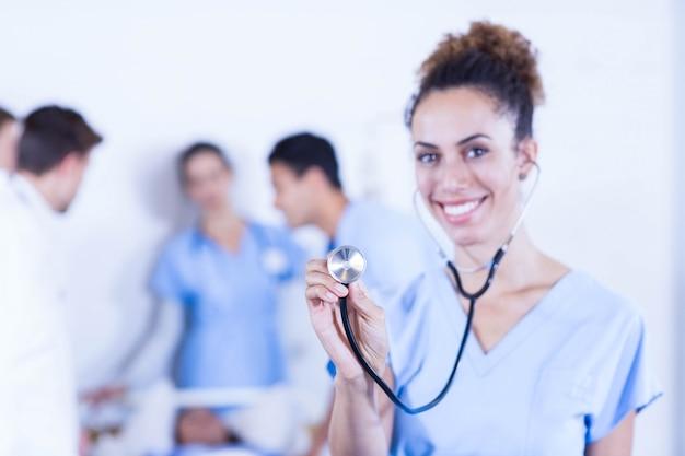 Retrato, de, doutores, ficar, com, braços cruzaram, e, outro, doutor, examinando, um, paciente, atrás de, hospitalar