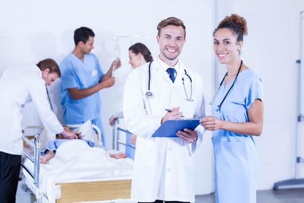 Retrato, de, doutores, segurando clipboard, e, sorrindo, enquanto, outro, doutor, examinando, um, paciente, atrás de, hospitalar
