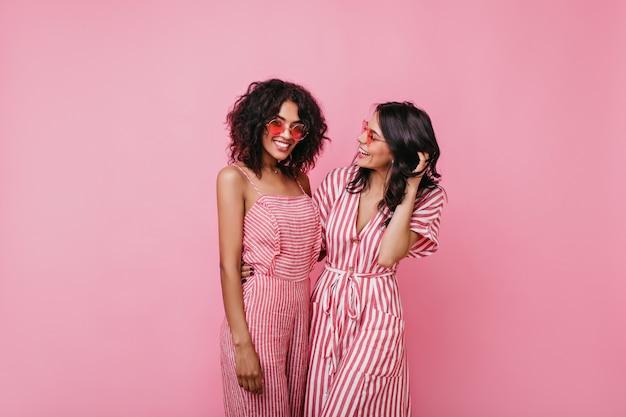 Retrato de duas alegres garotas africanas emocionais com cabelos cacheados. irmãs em vestidos de verão listrados se alegram.