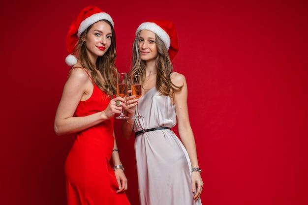 Retrato de duas amigas atraentes com cabelos longos ondulados em vestidos de seda vermelha e branca posando em gorros com taças de vinho rosé