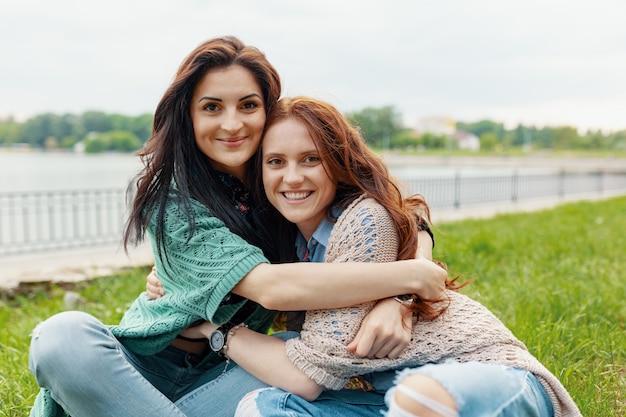 Retrato de duas amigas bonitas sorrindo abraços e se divertindo
