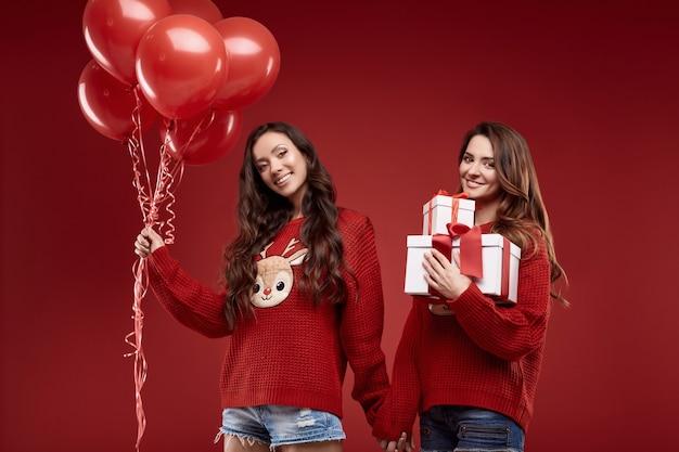 Retrato de duas amigas gêmeas malucas em suéteres de inverno aconchegantes com balões de festa e caixas de presente posando na parede vermelha